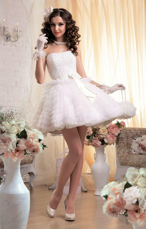 Стильное свадебное платье с бисерным декором корсета и пышной юбкой, покрытой оборками.