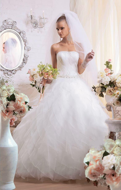 Открытое свадебное платье с прямым декольте и многослойным подолом с прозрачным верхом.