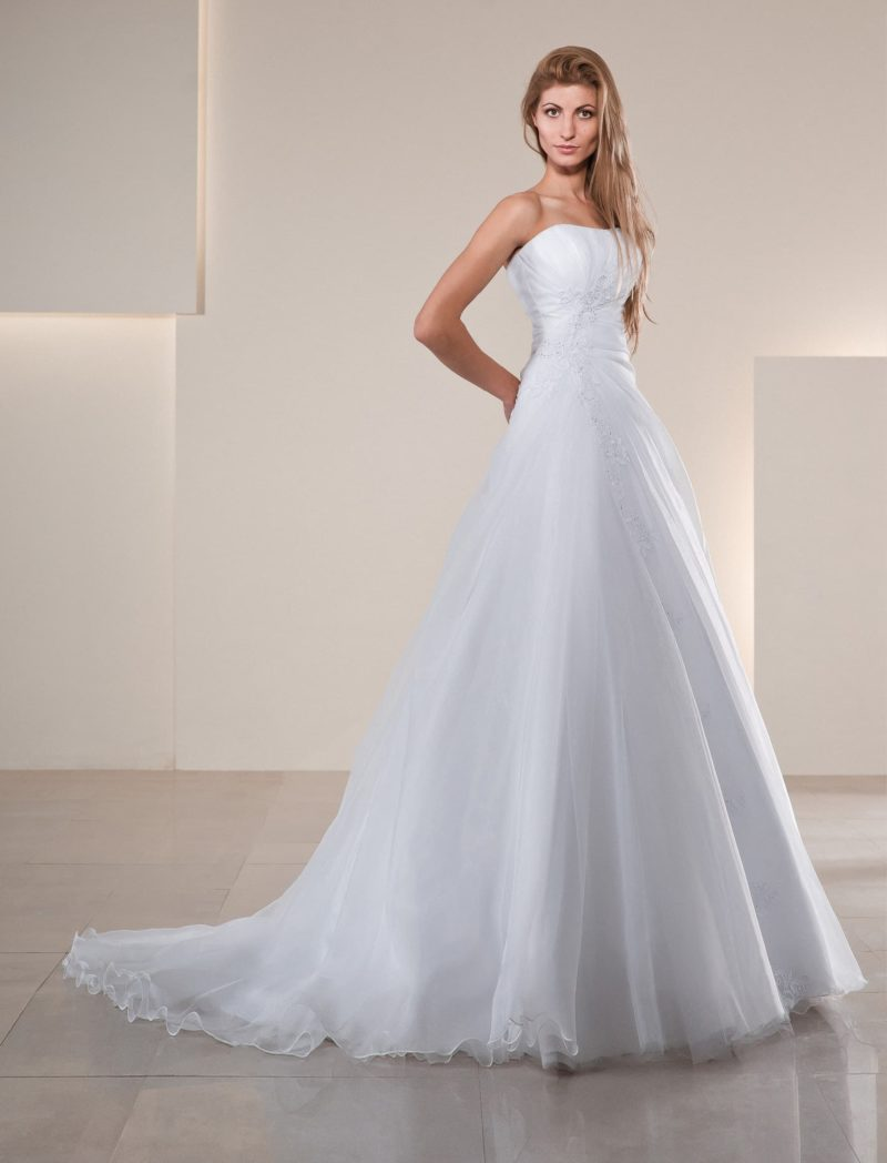 Сдержанное свадебное платье с многослойной юбкой и длинным полупрозрачным шлейфом.
