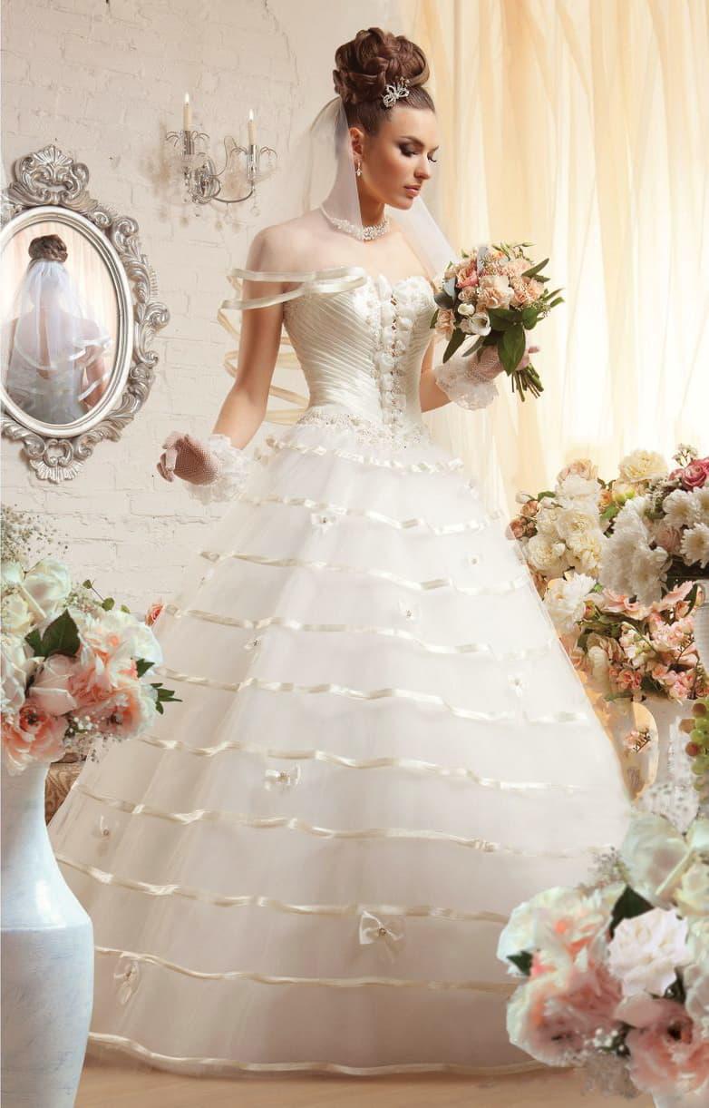 Открытое свадебное платье с бантами на корсете и атласным декором многослойной юбки.