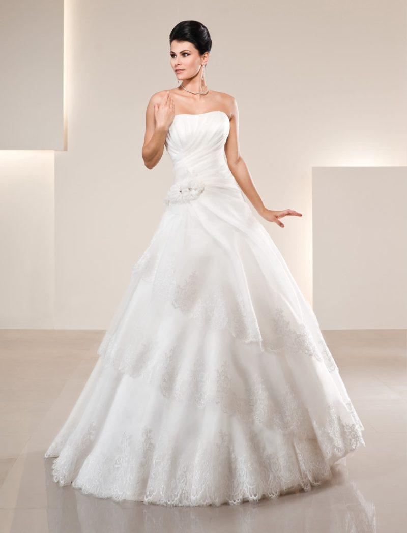 Свадебное платье с деликатным лифом, драпировками и многоярусной кружевной юбкой.