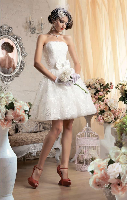 Короткое свадебное платье с кружевной отделкой и стильным открытым лифом прямого кроя.