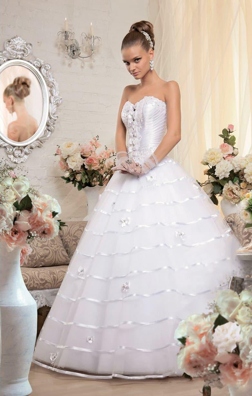 Торжественное свадебное платье с многослойной юбкой с атласным декором и открытым корсетом.