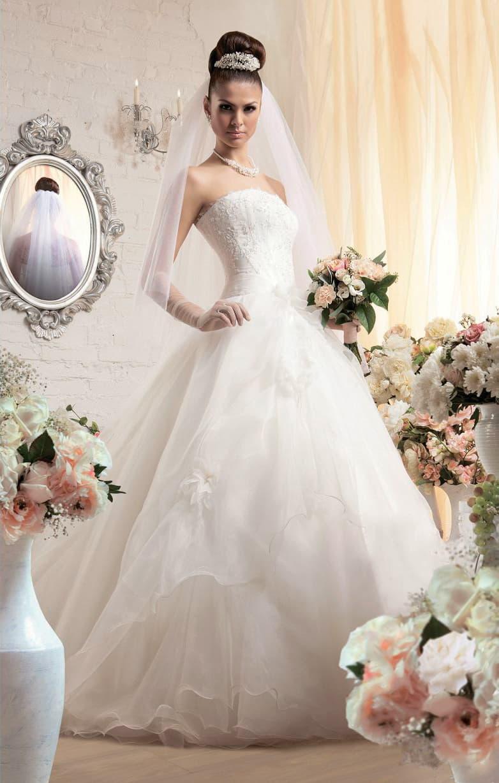 Традиционное свадебное платье с легкими оборками по подолу и открытым лифом прямого кроя.