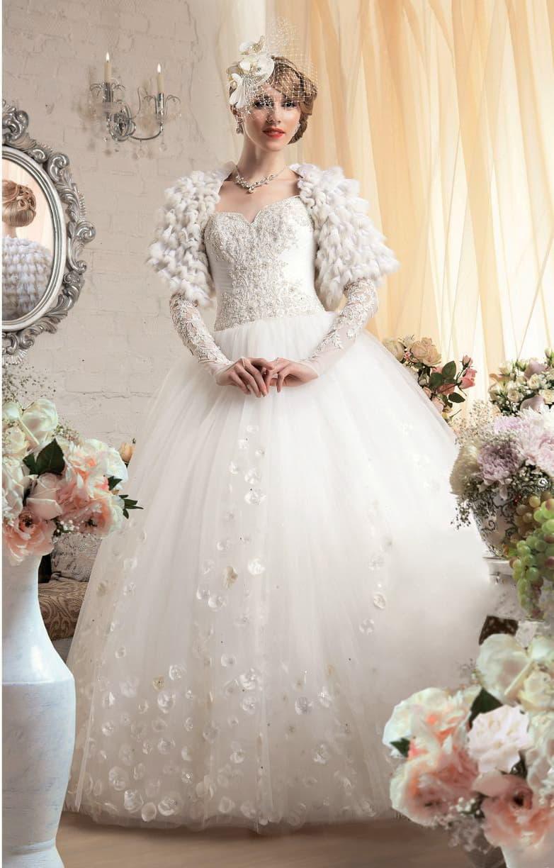 Необычное свадебное платье с пышным низом, украшенным атласными лепестками, и меховым болеро.