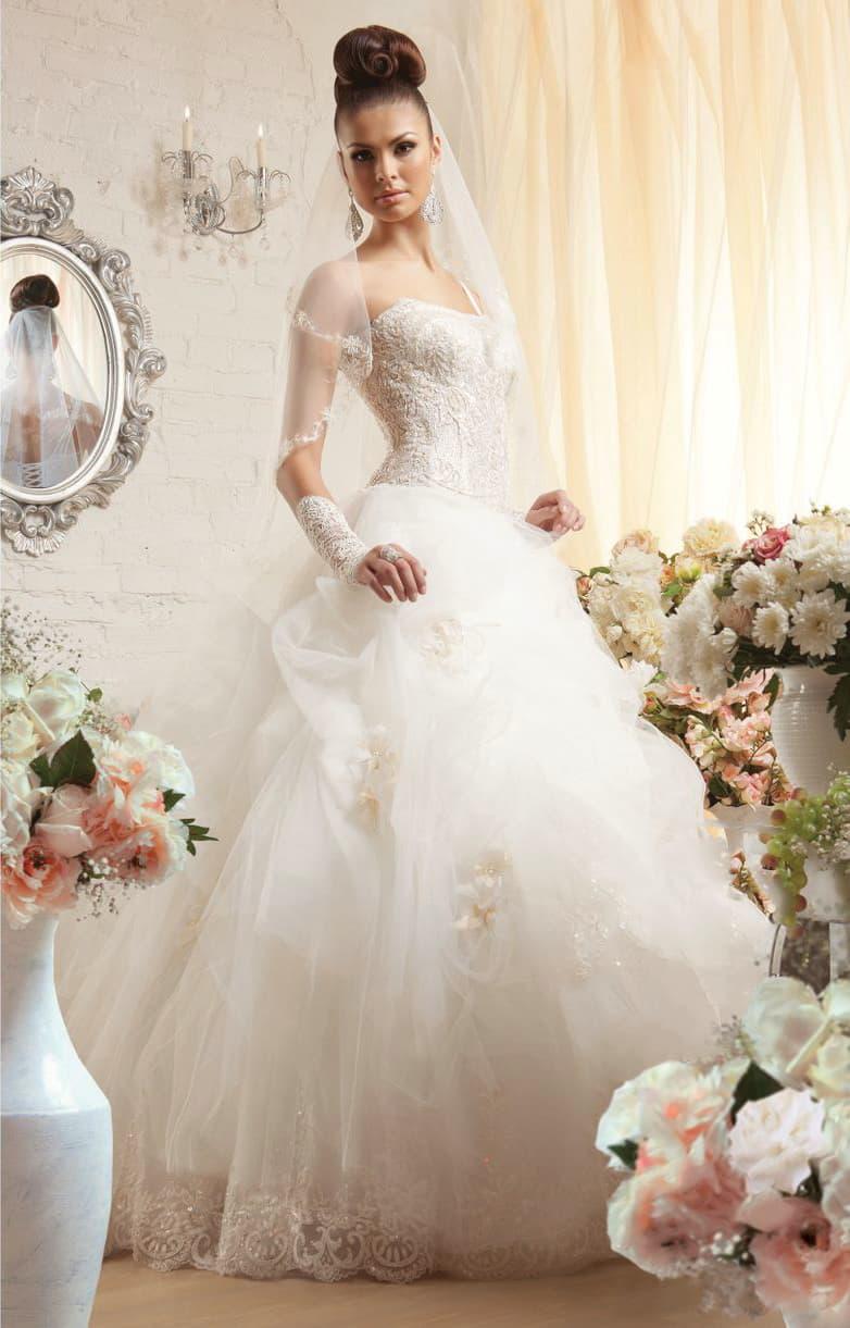 Пышное свадебное платье с открытым фактурным корсетом и объемной отделкой юбки.