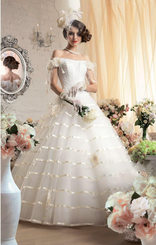 Открытое свадебное платье с пышным низом и эксцентричной отделкой глянцевым атласом.