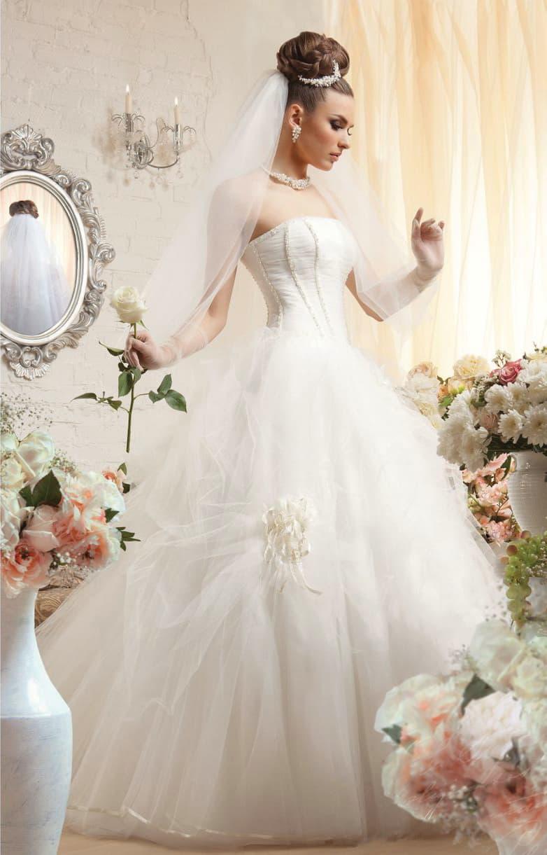 Свадебное платье с классическим открытым корсетом и полупрозрачной отделкой юбки.