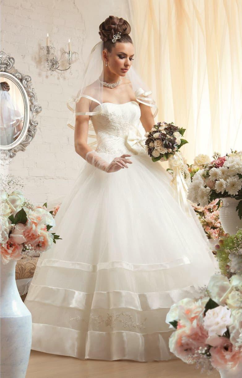 Открытое свадебное платье с воздушным низом, украшенным широкими атласными полосами.
