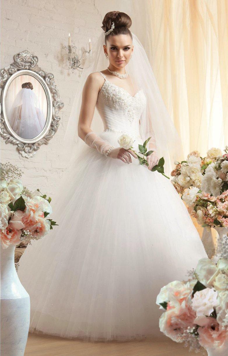 Роскошное свадебное платье с низом пышного кроя и открытым лифом, дополненным узкими бретелями.