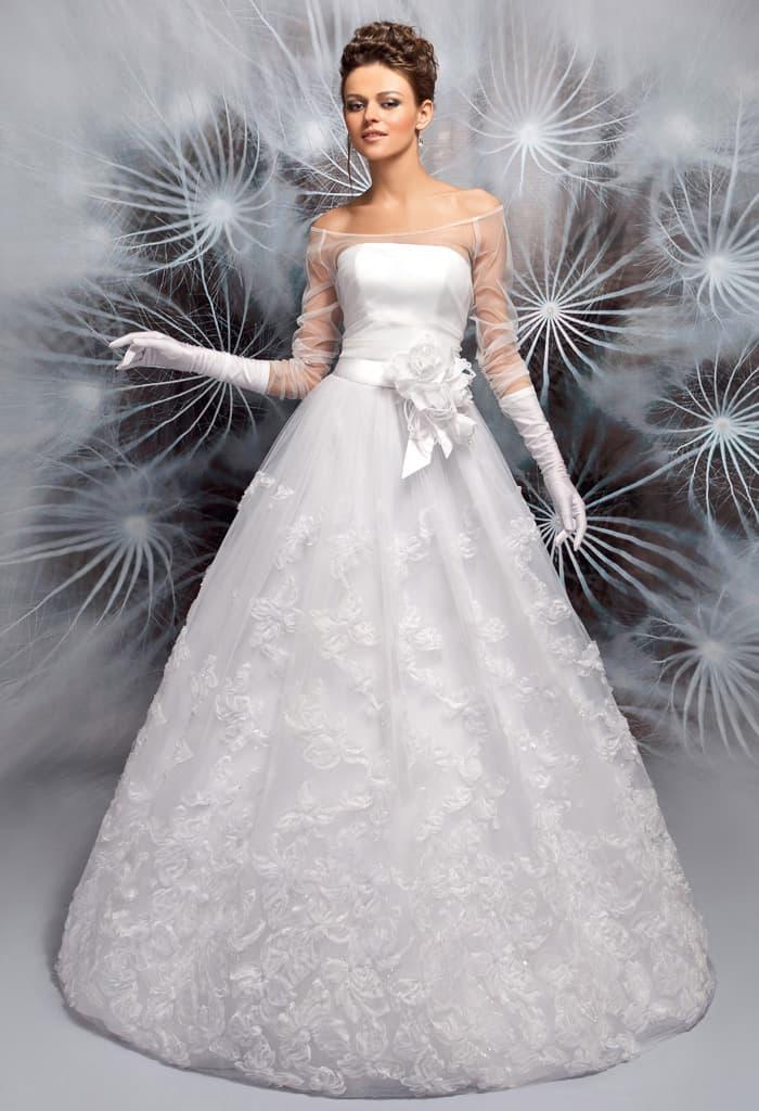 Выразительное свадебное платье с округлым декольте и объемной отделкой пояса.