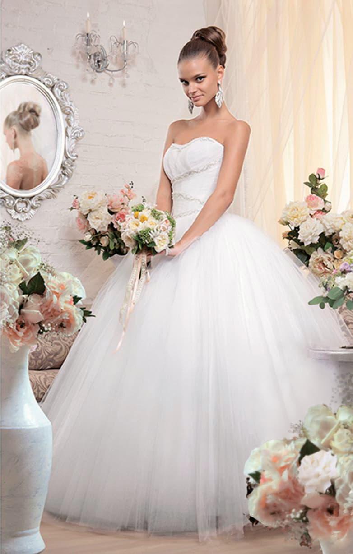 Сдержанное свадебное платье с пышным низом и лаконичным корсетом с бисерным декором.