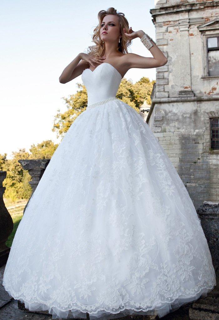 Утонченное свадебное платье с лифом в форме сердца и объемной кружевной юбкой.