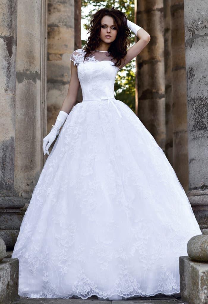 Закрытое свадебное платье с пышной юбкой, украшенной аппликациями.