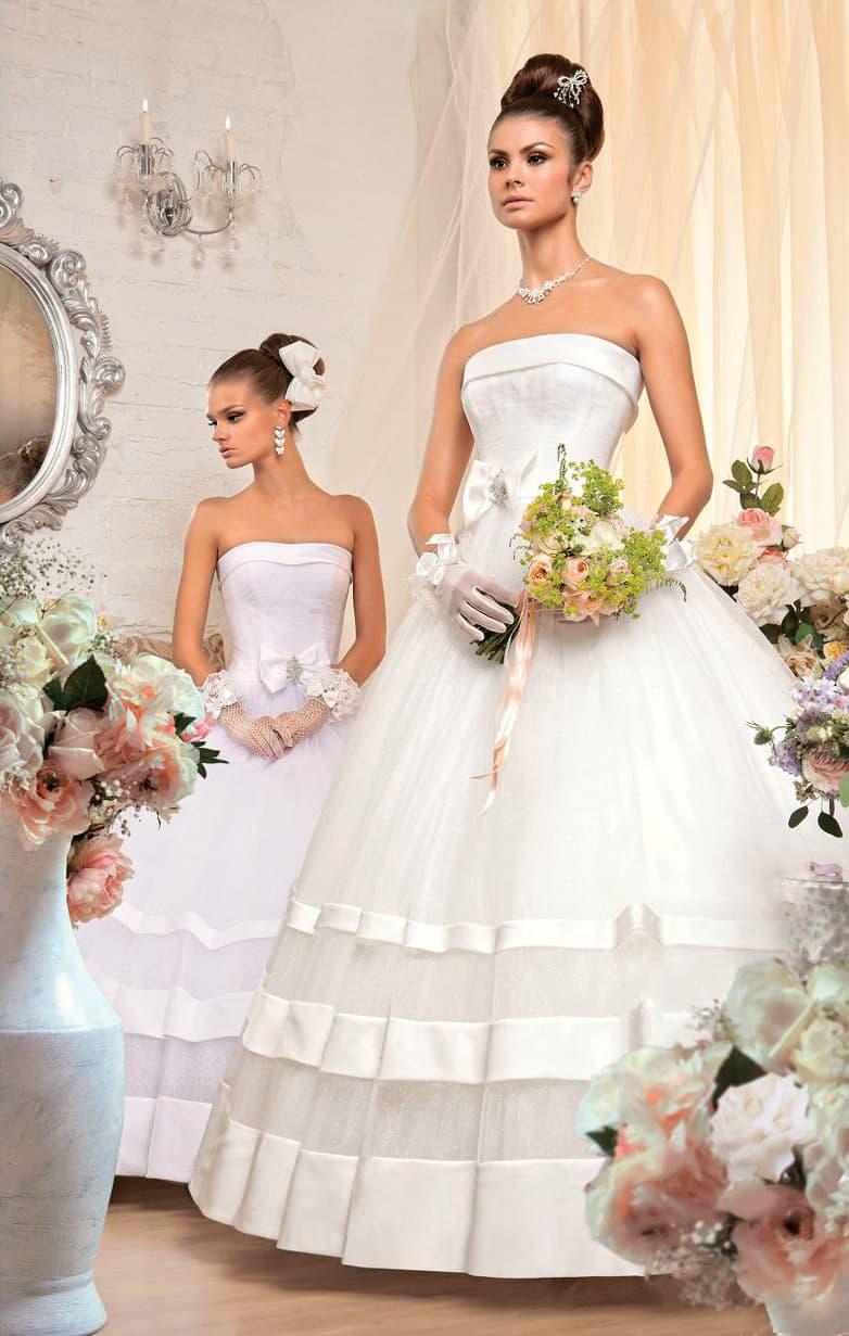Открытое свадебное платье с лаконичным корсетом и широкими атласными полосами отделки на юбке.