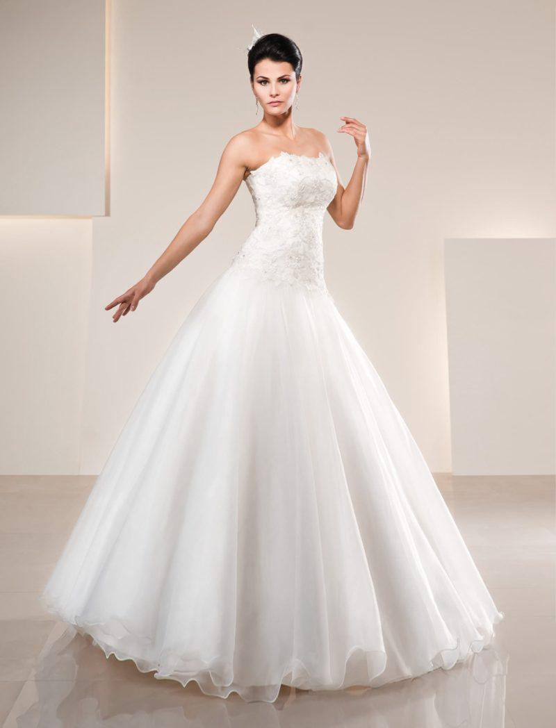 Кружевное свадебное платье с лифом прямого кроя и многослойной пышной юбкой.