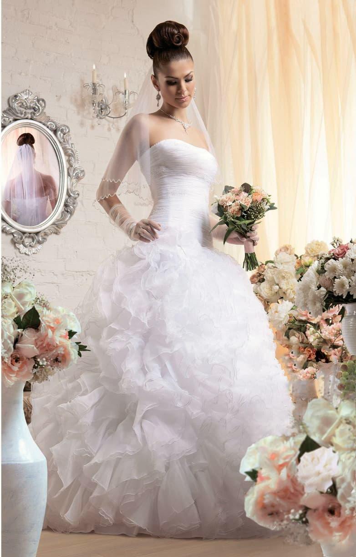 Воздушное свадебное платье с лаконичным открытым корсетом и оборками по подолу.