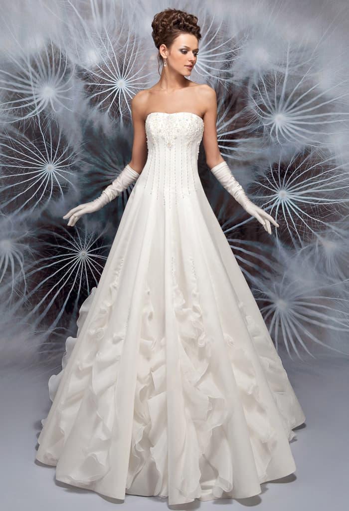 Необычное свадебное платье с оборками по низу подола и открытым лифом прямого кроя.