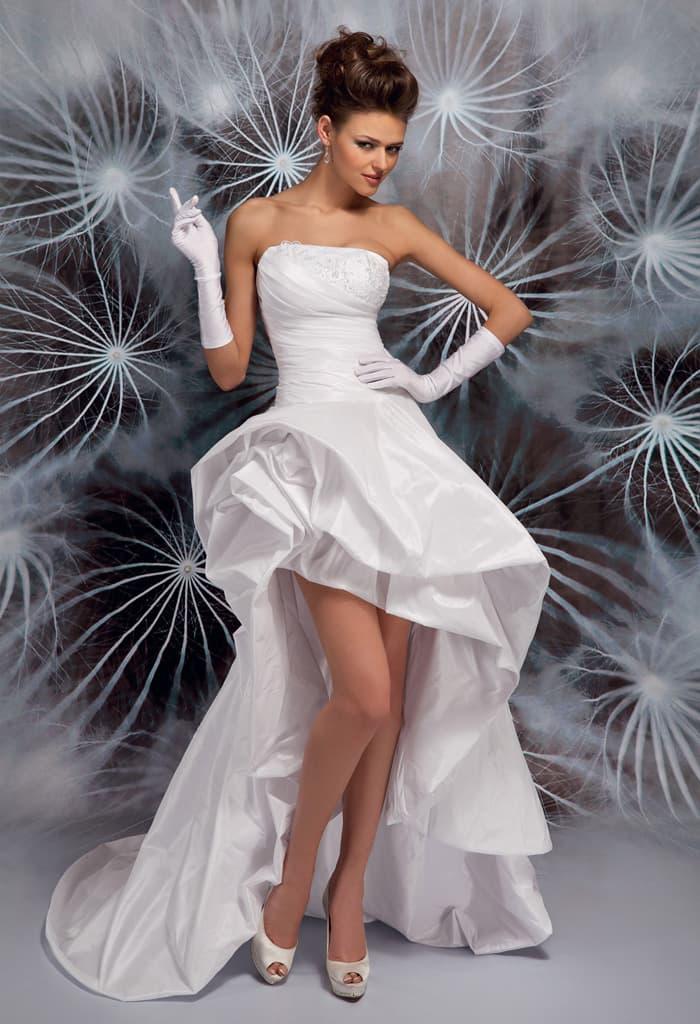 Экстравагантное свадебное платье с открытым верхом и укороченным спереди подолом.