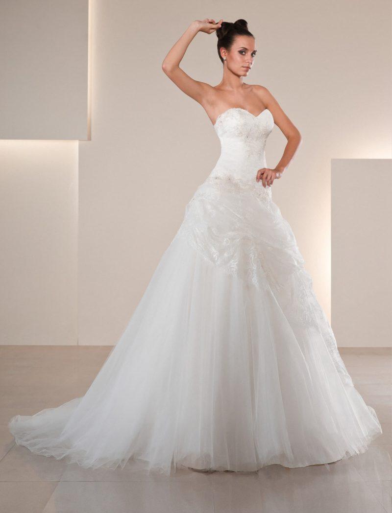 Открытое свадебное платье с лифом-сердечком и пышными кружевными оборками по подолу.