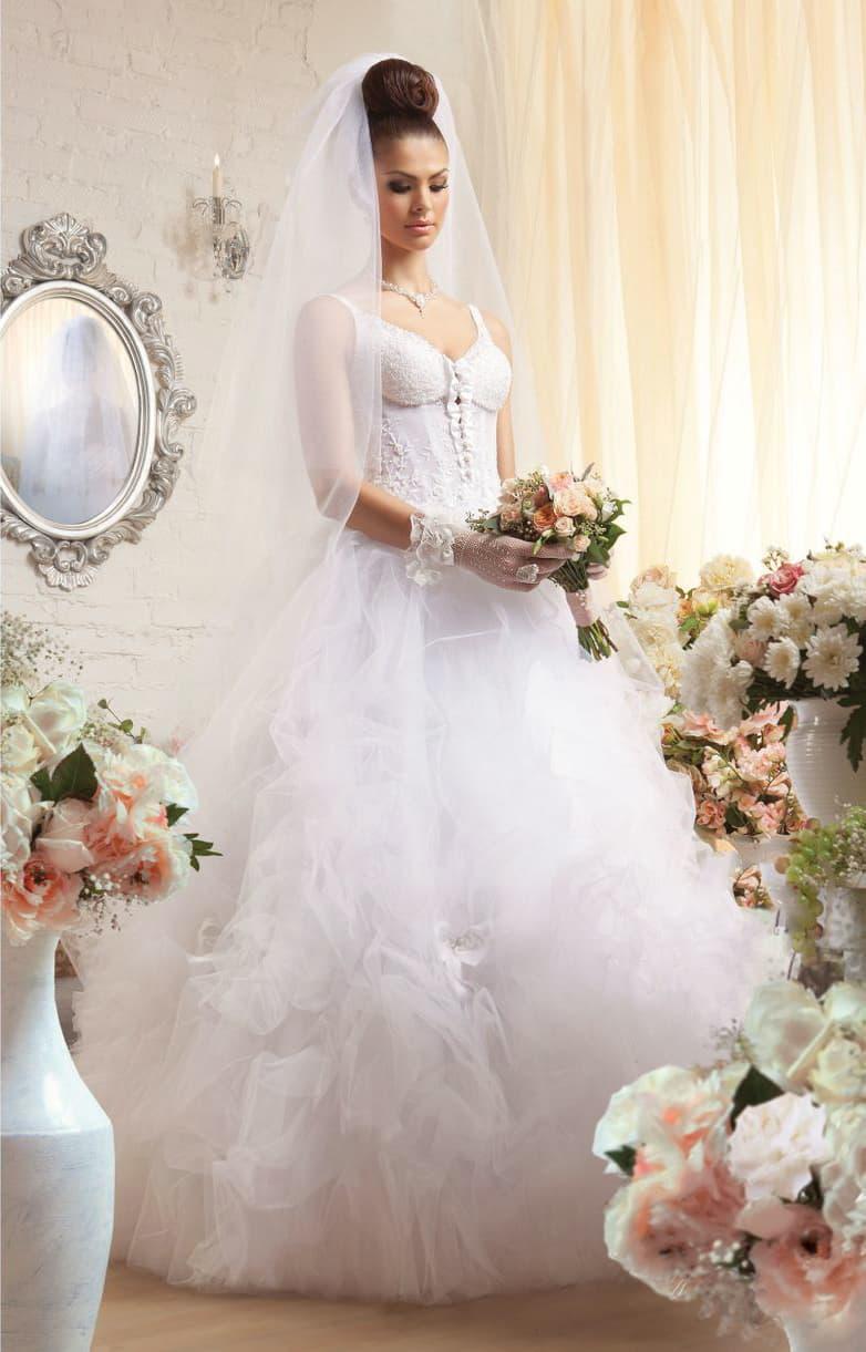 Изысканное свадебное платье с объемными прозрачными оборками и открытым лифом.