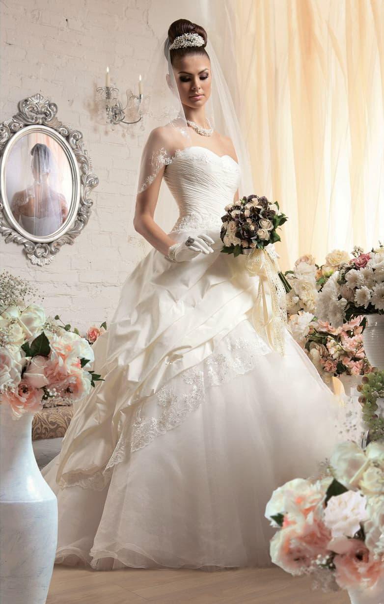 Драматичное свадебное платье с открытым корсетом и пышными складками по подолу.