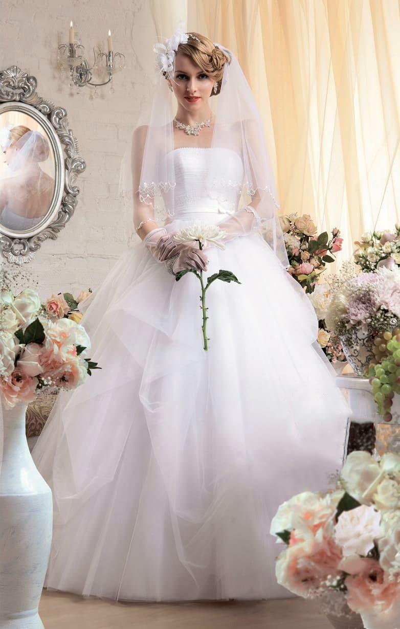 Роскошное свадебное платье с прямой линией декольте и прозрачными оборками по юбке.