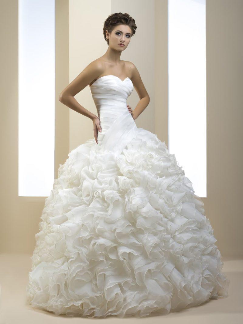 Впечатляющее свадебное платье с оборками на юбке и широкими драпировками на открытом корсете.