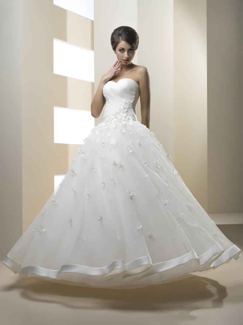 Пышное свадебное платье с объемными бутонами по подолу и открытым лифом в форме сердца.