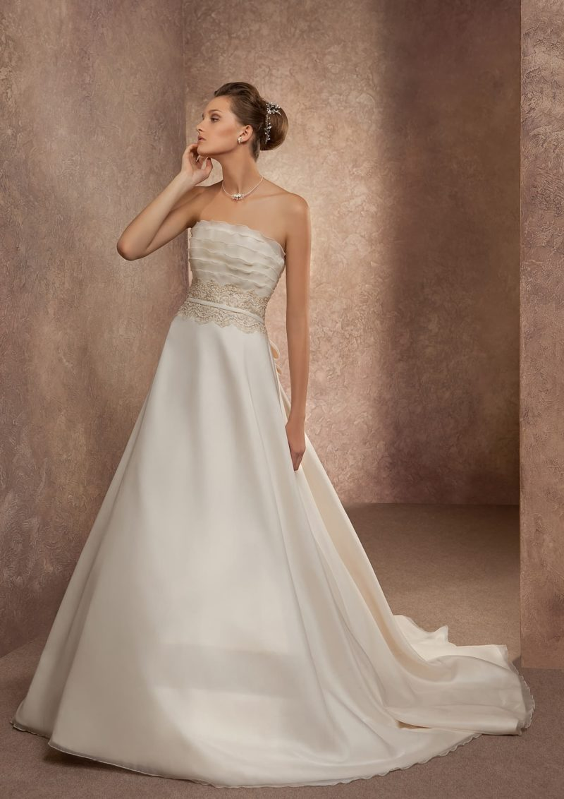 Свадебное платье оттенка слоновой кости с открытым корсетом, покрытым полупрозрачными оборками.
