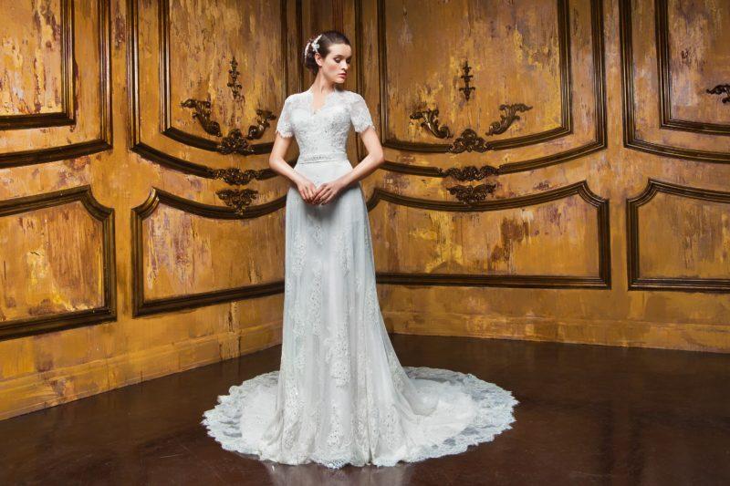 Прямое свадебное платье с закрытым лифом, короткими рукавами и длинным кружевным шлейфом.