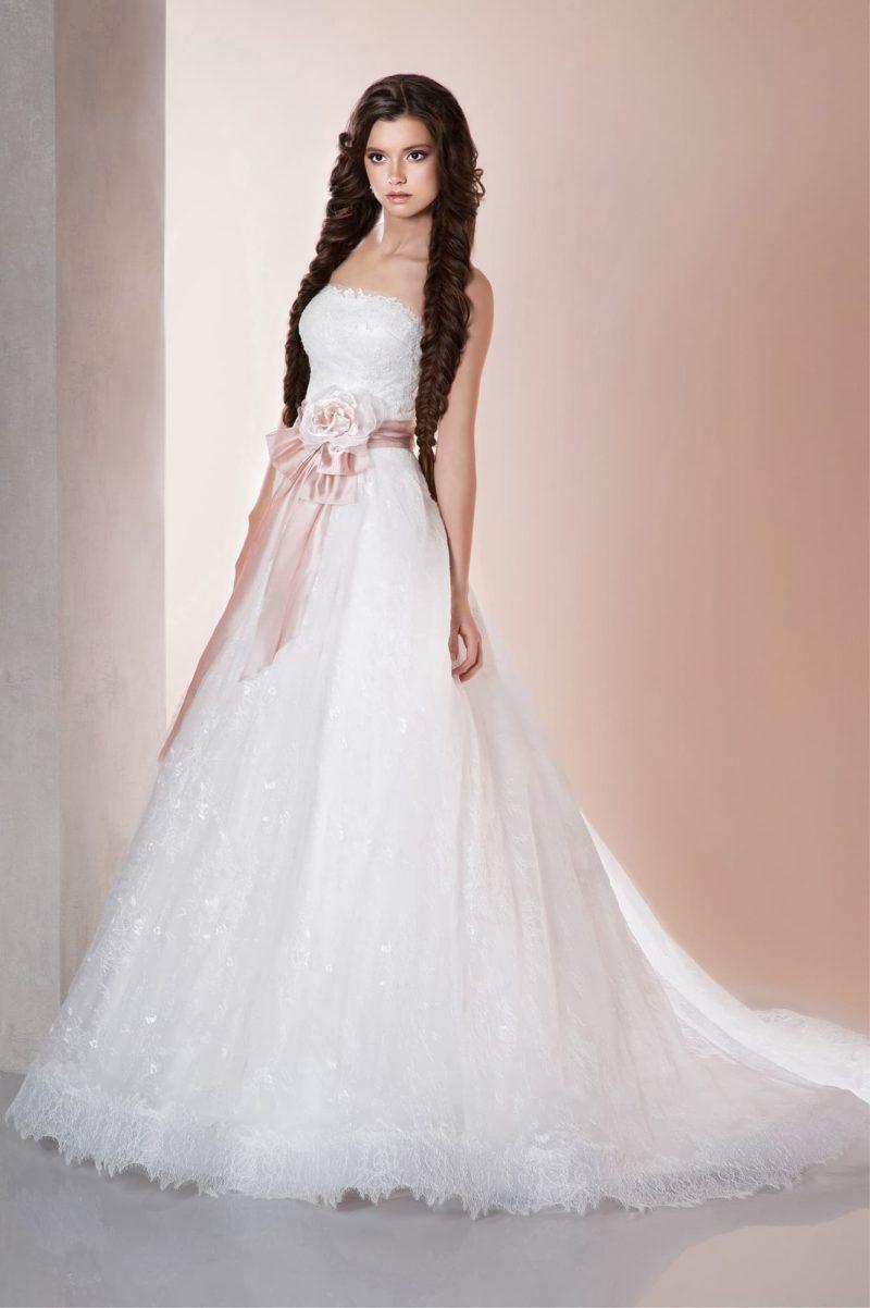 Романтичное свадебное платье с кружевным декором низа подола и широким розовым поясом.