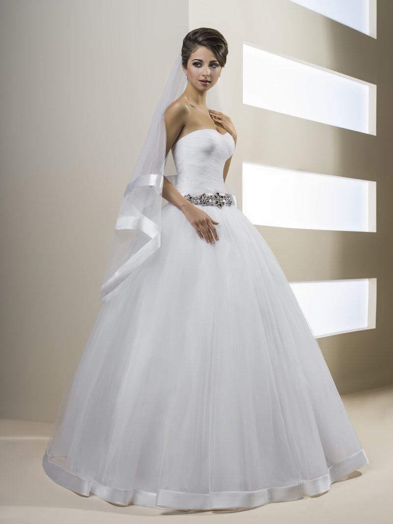 Изысканное свадебное платье пышного кроя с атласом по низу подола и открытым верхом.