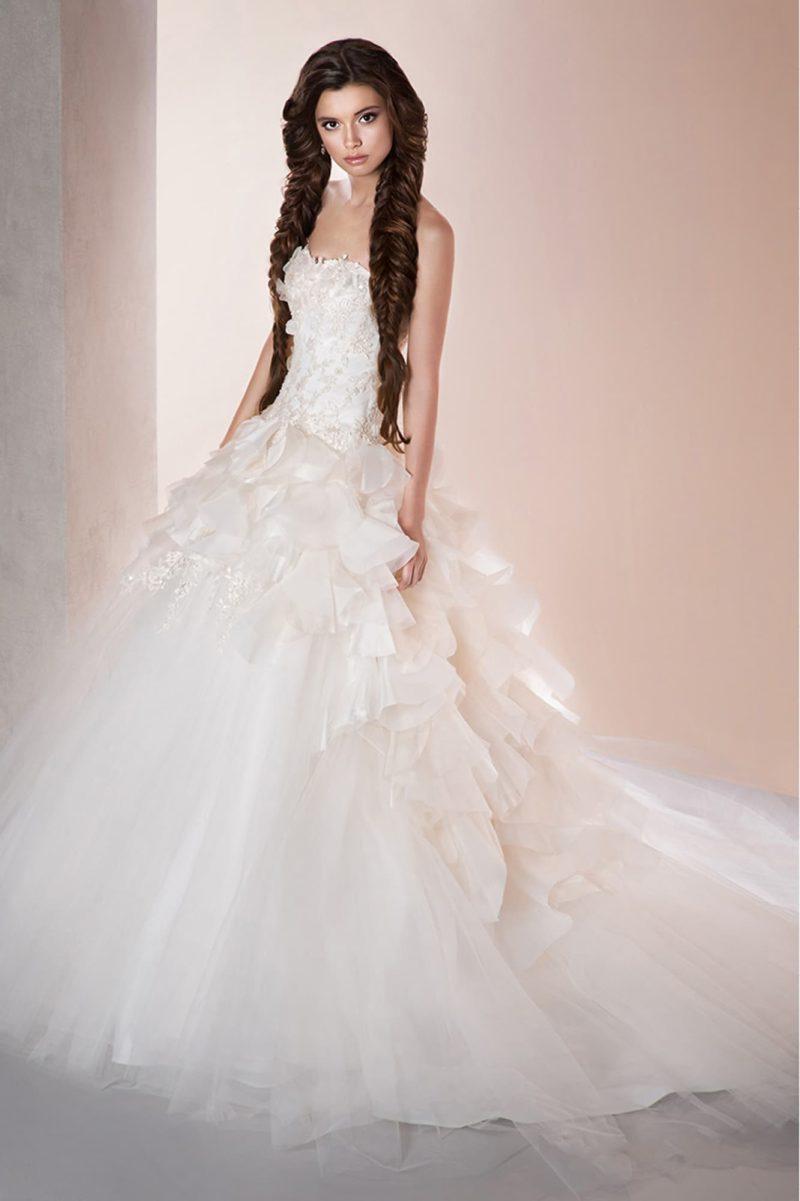 Открытое свадебное платье с объемной отделкой корсета и многослойной юбкой со шлейфом.