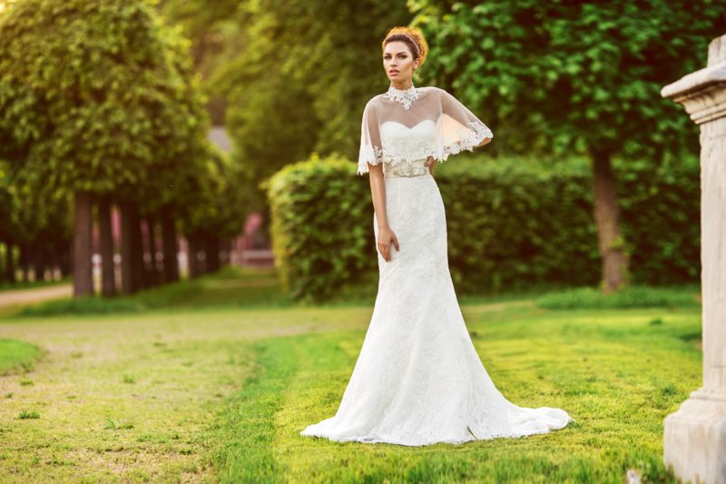 Стильное свадебное платье «русалка» с полупрозрачной накидкой над открытым лифом.