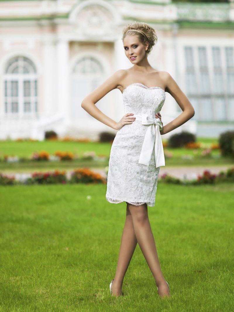 Короткое свадебное платье с кружевной отделкой, коротким болеро и широким атласным поясом.