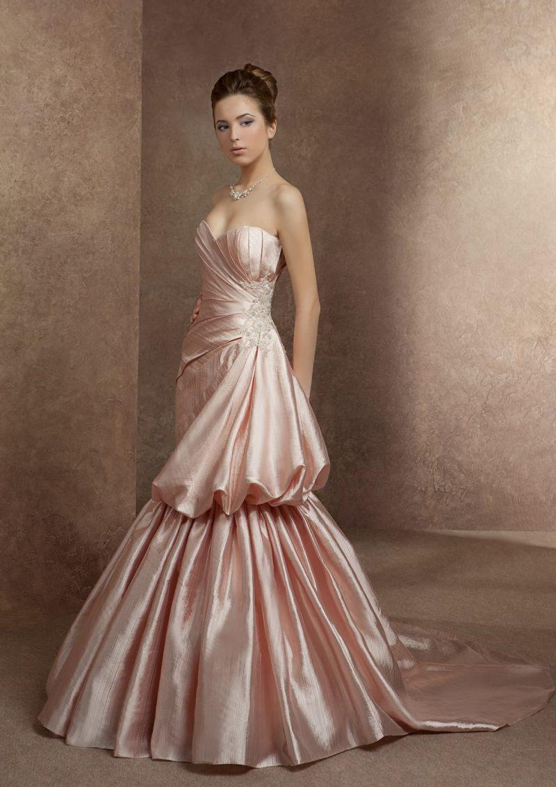 Атласное свадебное платье розового цвета с эксцентричной отделкой объемными складками ткани.
