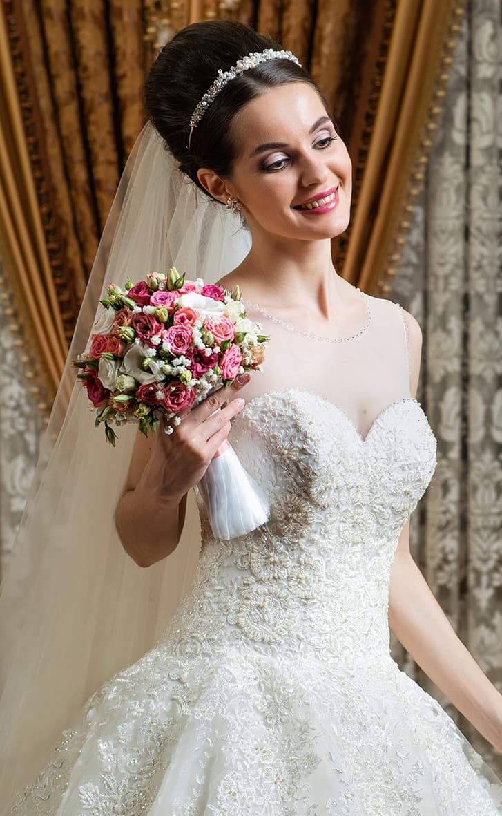 Свадебное платье с торжественным настроением, украшенной вышивкой и пуговицами на спинке.