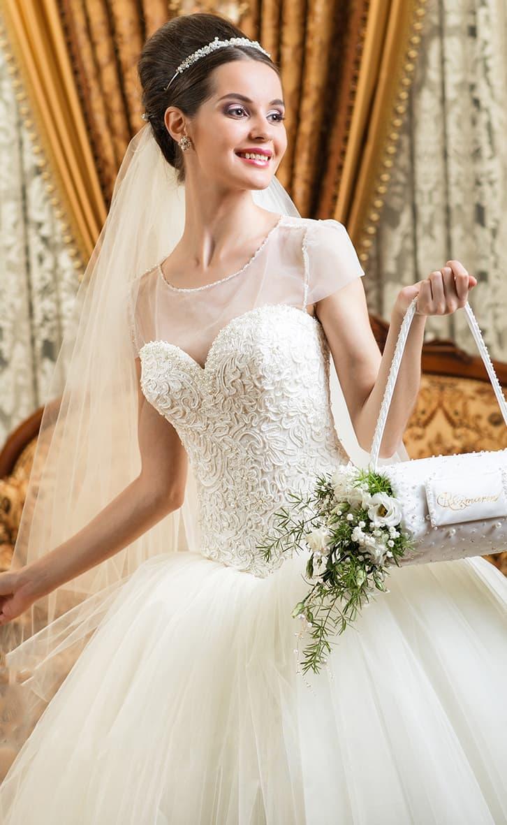 Свадебное платье с фактурным корсетом, прозрачными рукавами и пышным подолом.
