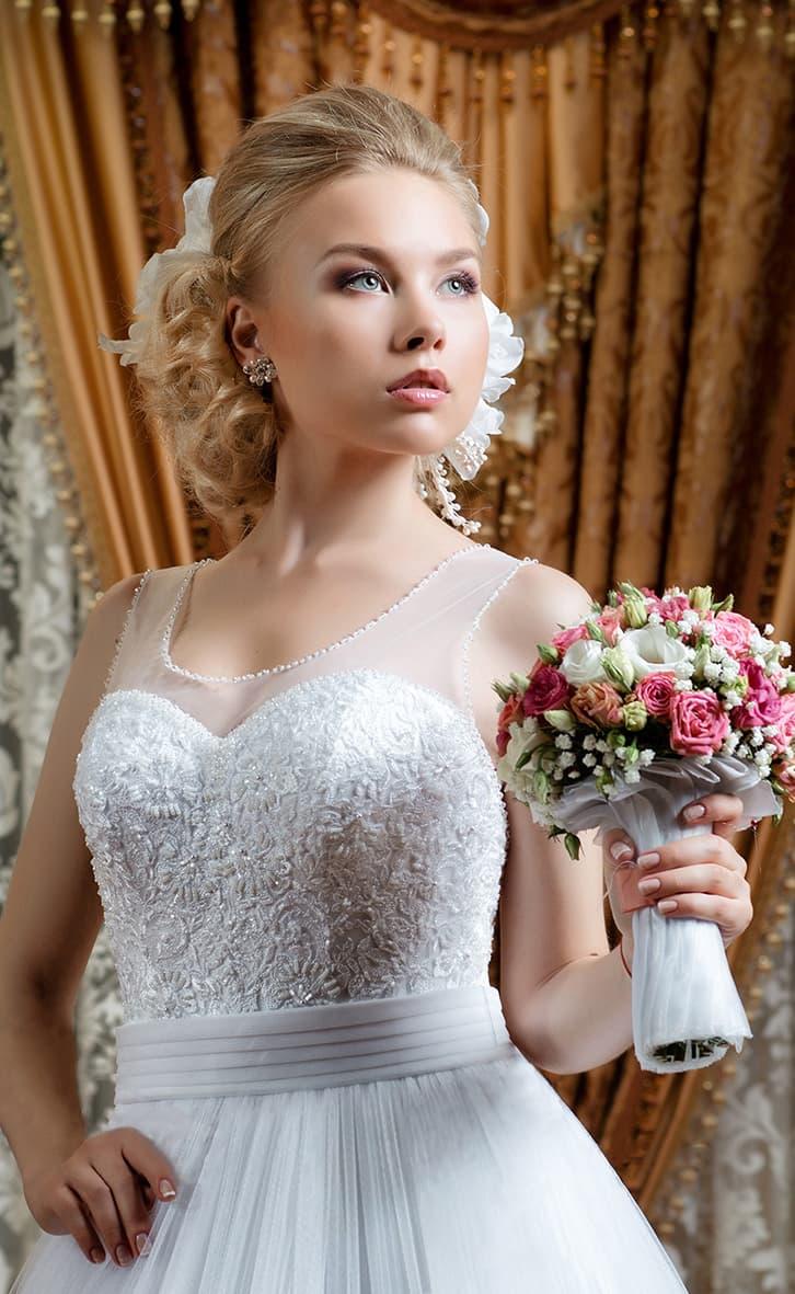 Пышное свадебное платье с широким поясом на талии и полупрозрачной отделкой над корсетом.