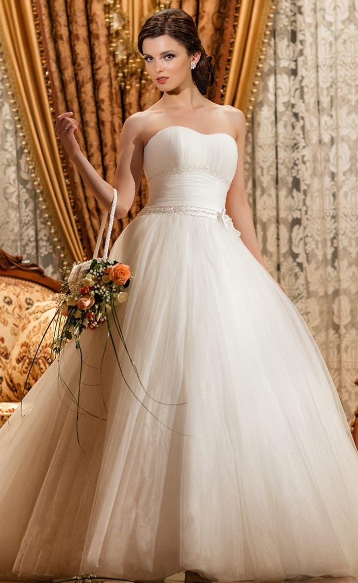 Пышное свадебное платье с открытым лифом и бисерным декором по атласному поясу.
