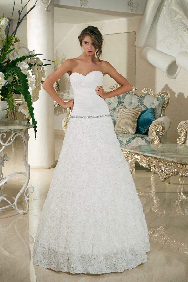 Свадебное платье с заниженной линией талии и объемным декором юбки А-силуэта.