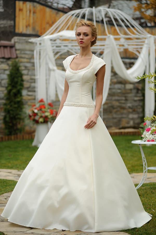 Фактурное свадебное платье с заниженной талией и коротким рукавом.