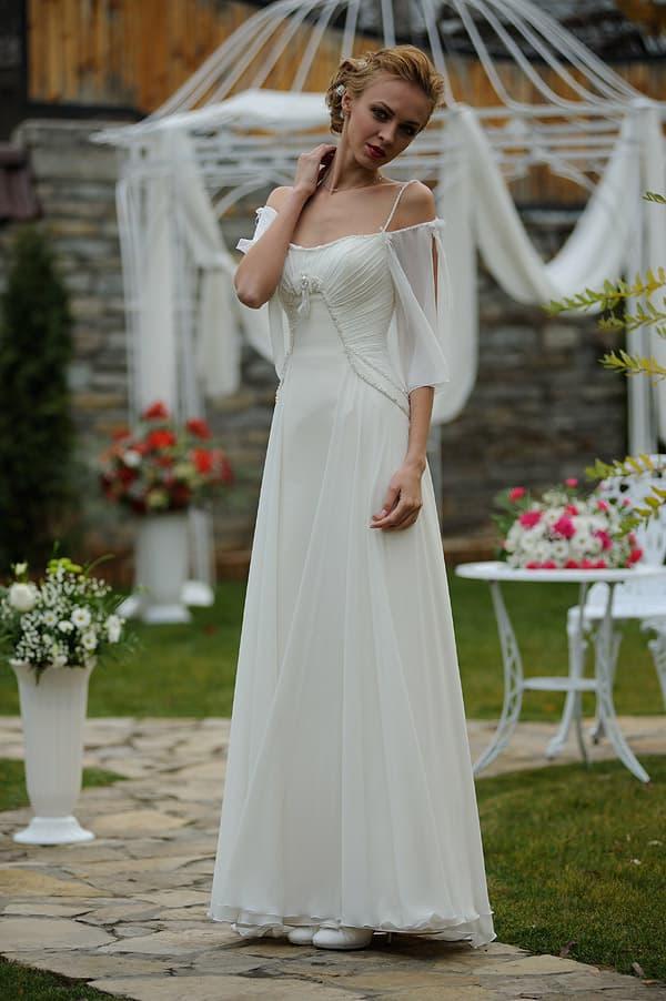 Прямое свадебное платье с необычным полупрозрачным рукавом и узкими бретелями.