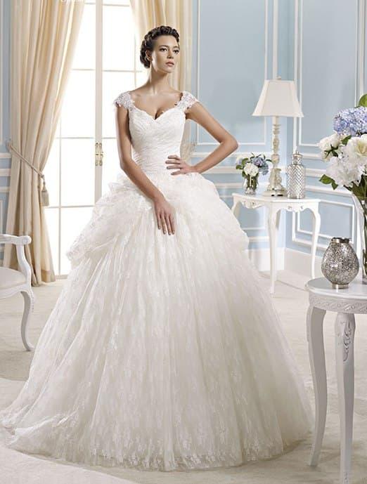 Кружевное свадебное платье с широкими бретелями и пышным низом.