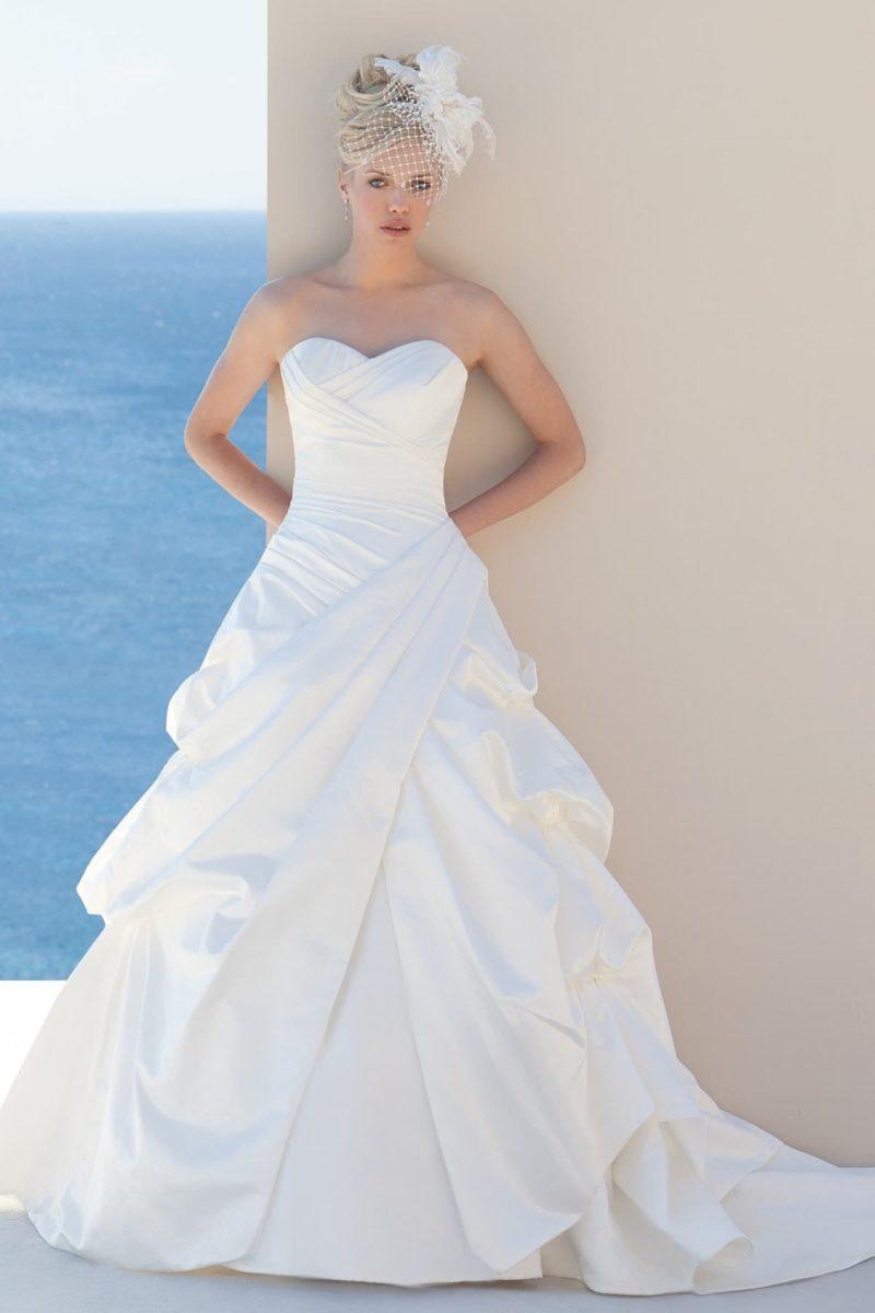 Свадебное платье пышного кроя, покрытое волнами и драпировками по всей длине.
