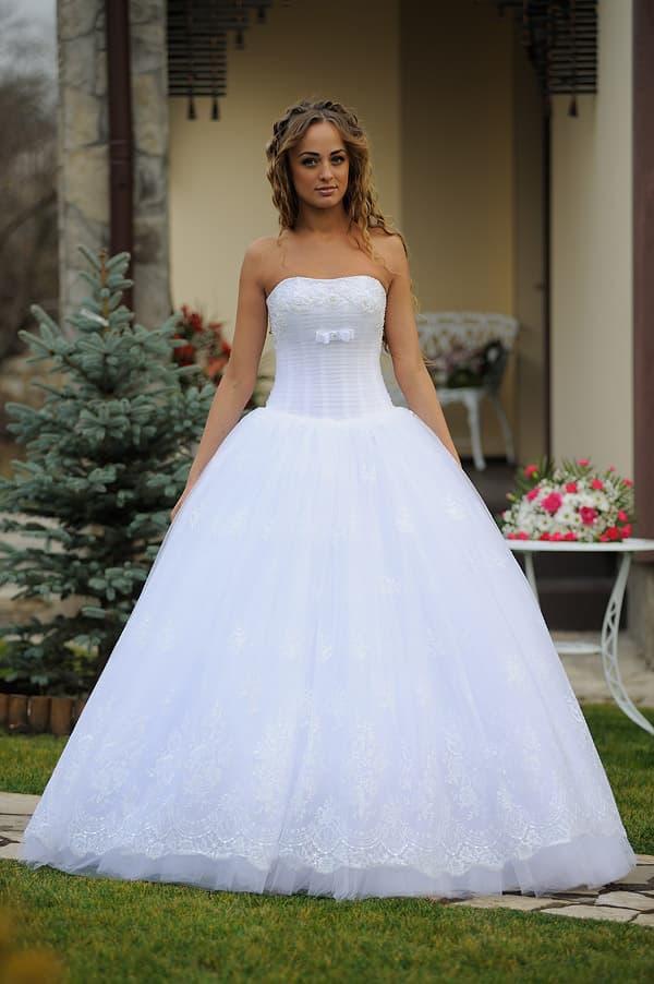 Роскошное свадебное платье с кружевным декором юбки и открытым вырезом.