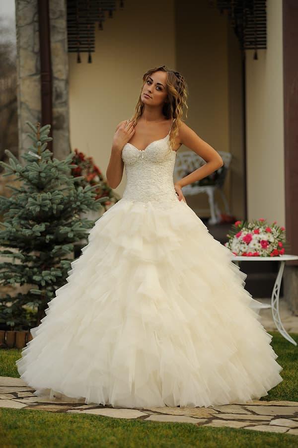 Пышное свадебное платье цвета слоновой кости с открытым фактурным лифом.
