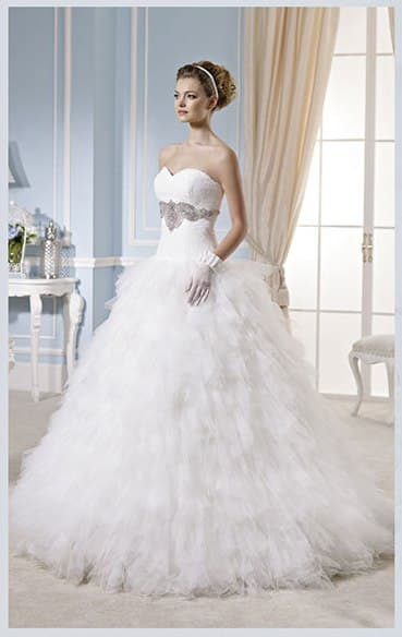 Пышное свадебное платье с кокетливым декором юбки и вышивкой под лифом.