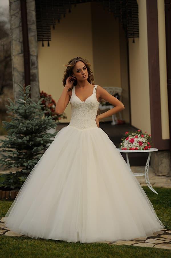 Свадебное платье на лямках с лифом-сердечком, дополненным бретелями, и пышной юбкой.